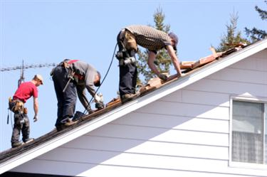 Roof Installation in Otway OH. Three roofers laying new shingle on a roof in Otway.